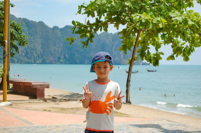 Portrait Of Boy Gesturing Peace Sign At Promenade