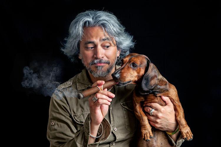 Portrait of man holding dog against black background