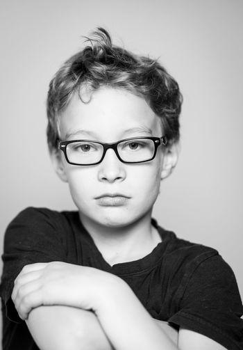 Portrait of boy wearing eyeglasses against gray background