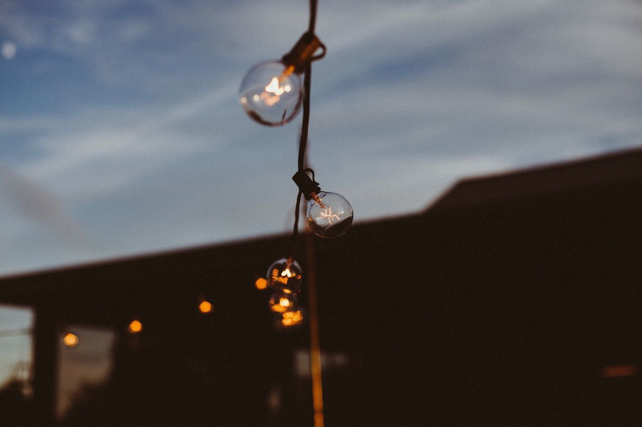 Low angle view of light bulbs against sky