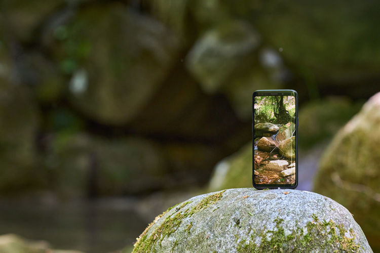 Close-up of smart phone on rock