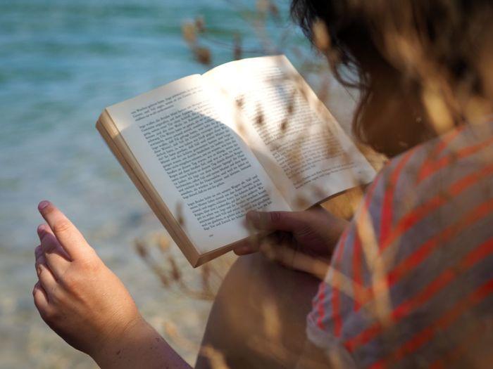 Girl reading book against lake