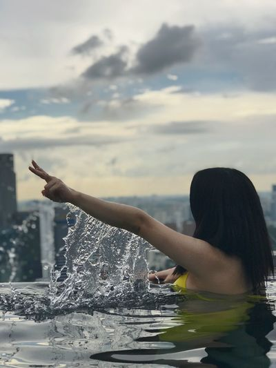 Woman swimming in infinity pool against sky