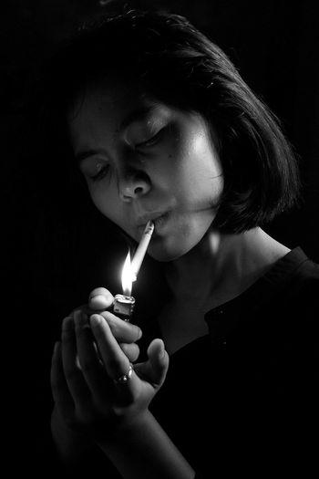 Close-up of woman lighting cigarette using lighter