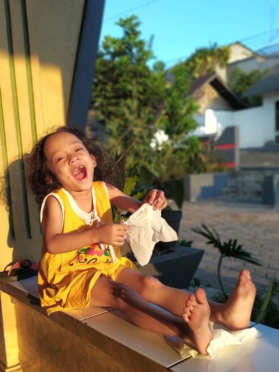 Portrait of playful girl sitting and playing with tissue paper