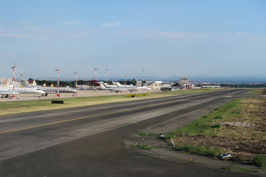 Rome Italy 19 June 2016. Private jets parked by the runway of Ciampino airport. The air traffic control of Aeroporto G. B. Pastine is visible in the background. Shot from inside airplane window. Aeroporto G. B. Pastine Air Traffic Control Tower Airport Airport Photography Airport Runway Airport Waiting Airportlife Airportphotography Airports Aviation Aviationphotography Capital Cities  Flights From Rome Flights To Rome Italia Italy Jets Mode Of Transport Private Jets Roma Rome Airport Rome Ciampino Airport Rome, Italy Runway Sky Moving Around Rome