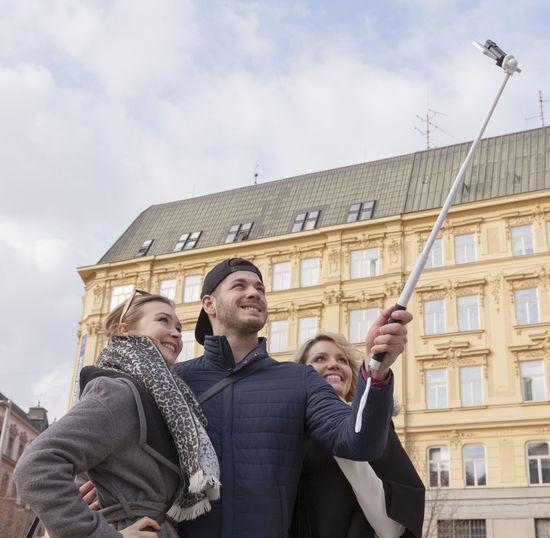 Happy friends taking selfie in city