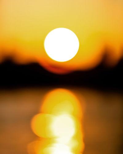 Defocused image of sun against sky during sunset
