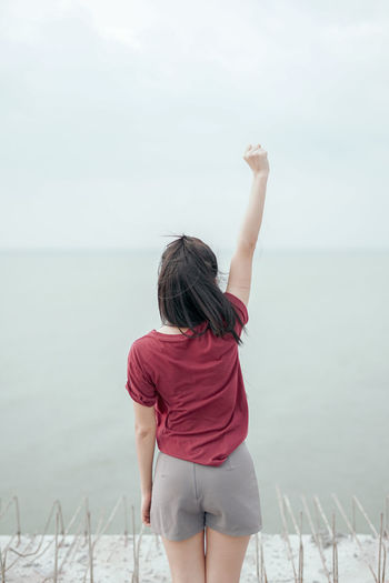 Rear View Of Woman With Hand Raised Standing At Beach Against Sky