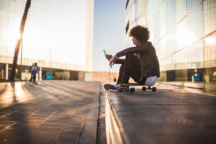 Man sitting in city against sky
