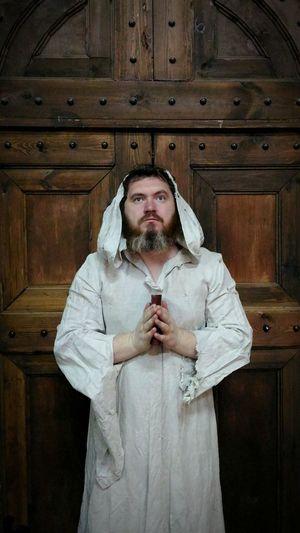 Priest holding bible against closed door