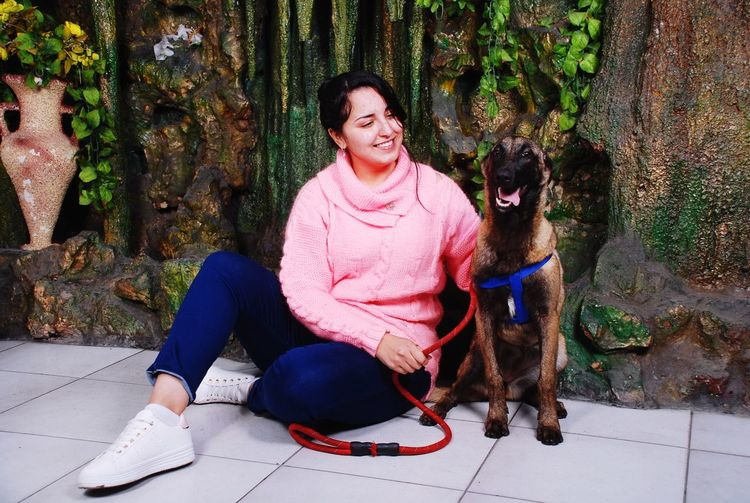 Smiling woman with dog sitting on floor against wall
