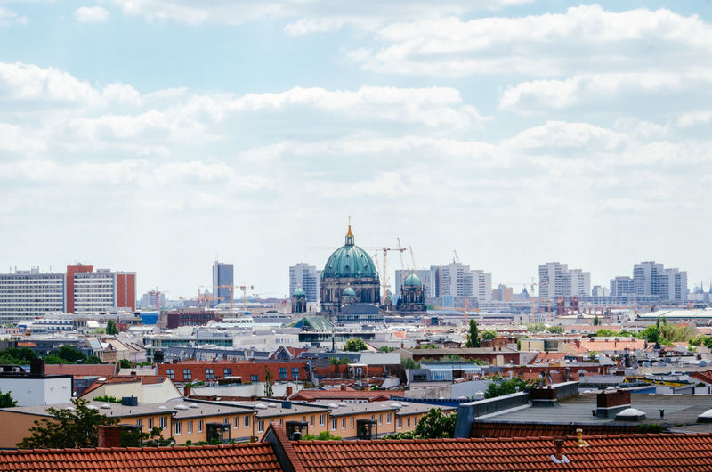 Berlin cathedral amidst buildings in city against cloudy sky