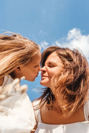 Close-up of daughter kissing mother against sky