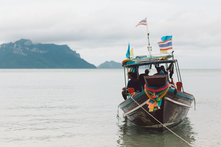 Water Transportation Mode Of Transportation Nautical Vessel Sky Scenics - Nature Waterfront Mountain Nature Sea Beauty In Nature Day Cloud - Sky Travel Real People Men Flag Outdoors Non-urban Scene