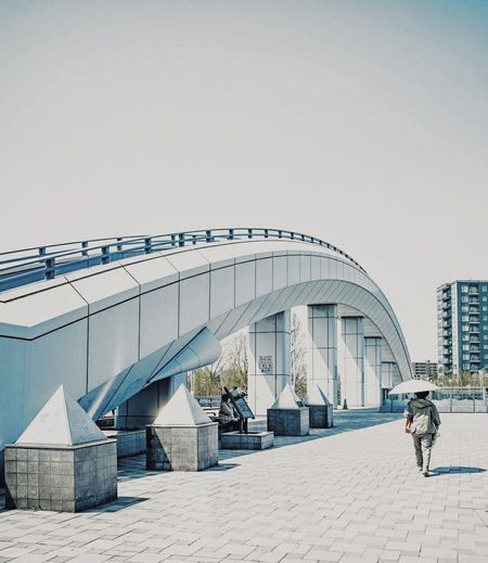 Rear view of people walking on bridge in city against clear sky