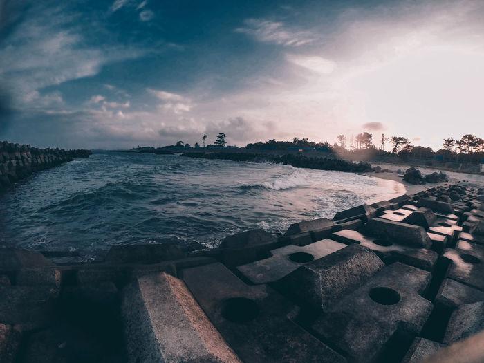 Seascape And Concrete Block Against Sky