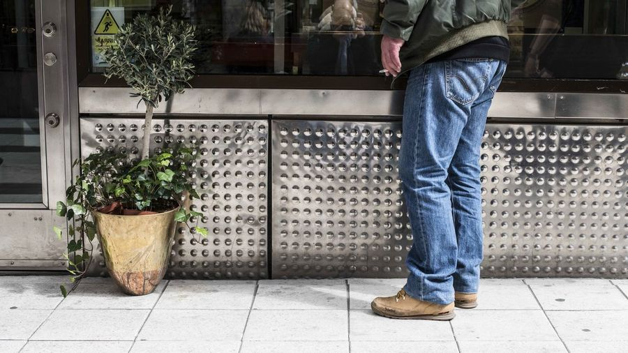 Low section of man standing on potted plant