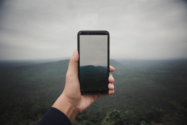 Hand of person photographing landscape from smart phone