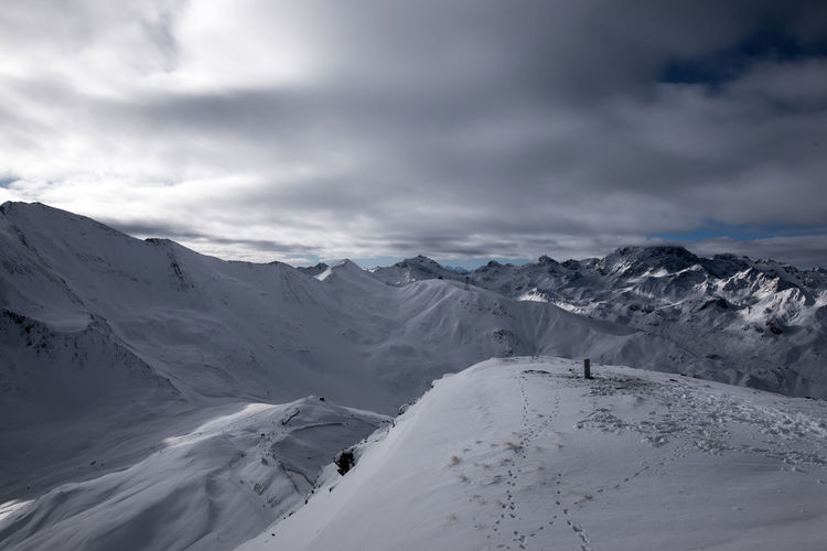 Scenic view of snowy mountains against cloudy sky