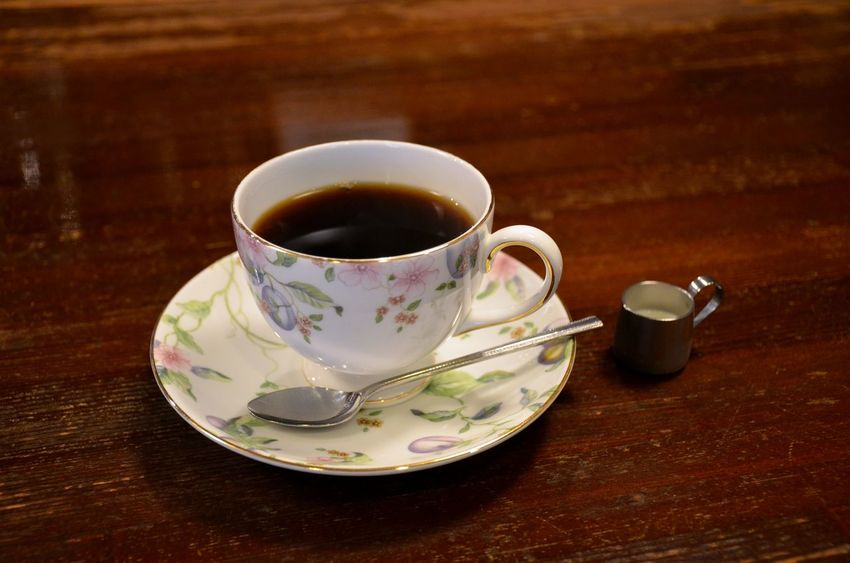 A delicate floral print porcelain cup of coffee with a miniature cream pot and small spoon at the counter of a coffee shop in Japan Food And Drink Tea Cup Coffee Cup No People Floral Pattern Teaspoon Coffee Japan Travel Restaurant Counter Diner Miniature Objects