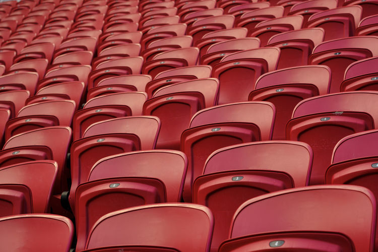 Empty red plastic seats in an empty stadium. many empty seats for spectators in the stands.