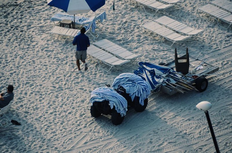 High angle view of towels and parasol on vehicle at beach