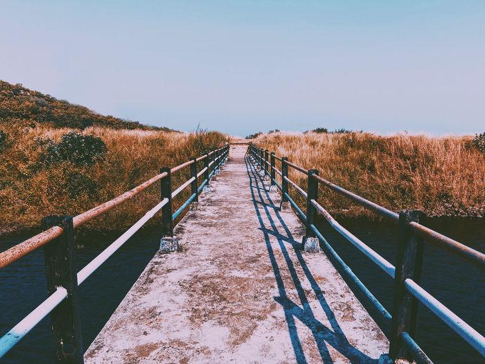 Footbridge over landscape against clear sky