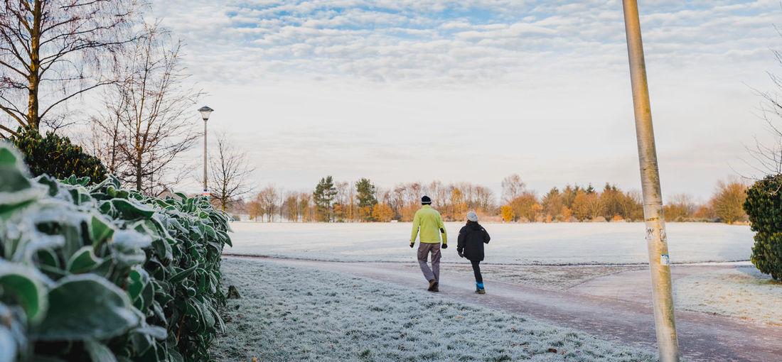 Rear view of people walking on snowy field against sky