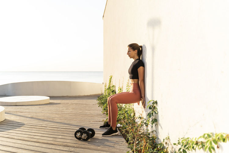 Side view of woman looking away while sitting on wall
