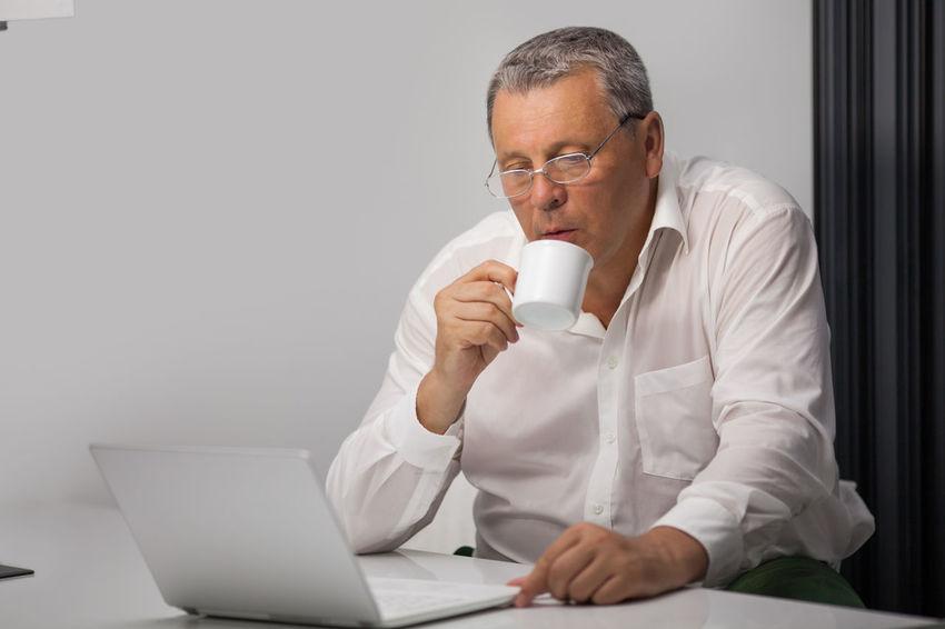 Break Business Businessman Businesspeople Caucasian Coffee Time Computer Concentrated Horizontal Internet Job Laptop Laptops Man Managing Office Senior Tea Use Work