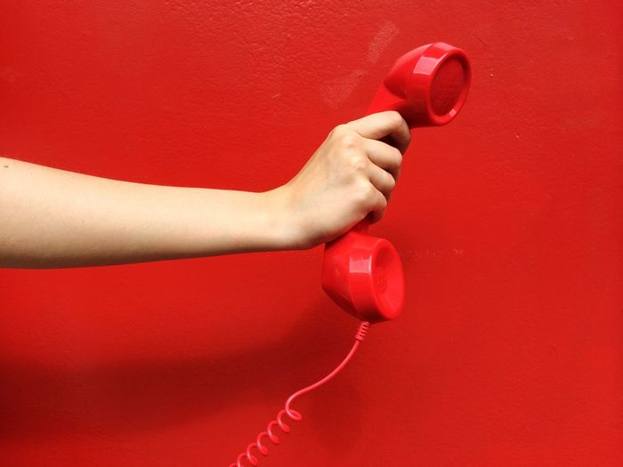Cropped hand of woman holding telephone receiver against red wall