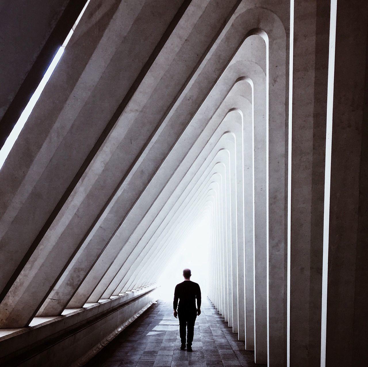 REAR VIEW OF PEOPLE WALKING IN TUNNEL
