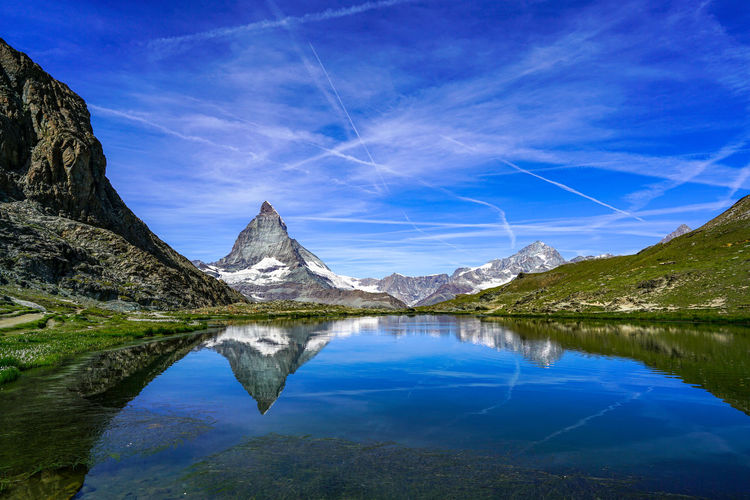 Reflection of mountain in lake against blue sky