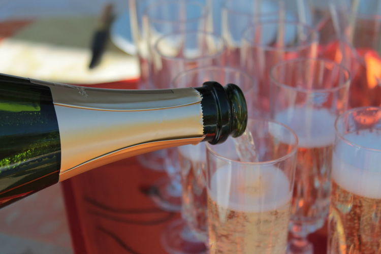 Close-up of champagne pouring from bottle in glass