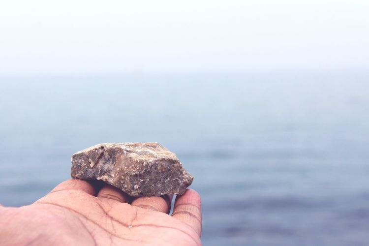 Close-Up Of Hand Holding Stone Against Sea