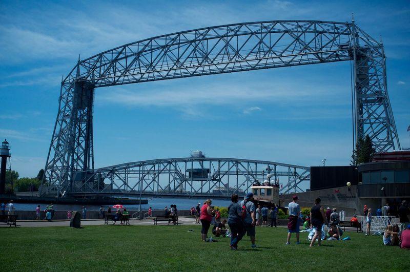 People in canal park visiting aerial lift bridge against sky