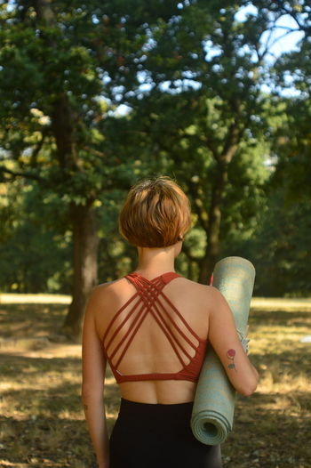 Rear view of woman standing with exercise mat against trees