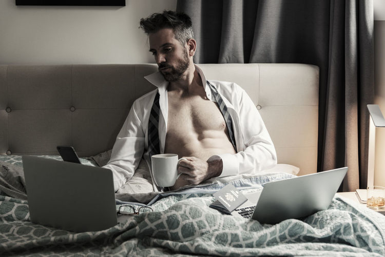 Very handsome fit muscular man working using computers while resting in bed with open shirt and tie holding a cup of coffee. Caffeine Coffee Beard Bedroom Businessman Coffee Cup Communication Computer Connection Indoors  Internet Laptop Leisure Activity Lifestyles Muscular One Person People Professional Real People Shirtless Sitting Technology Using Laptop Wireless Technology Young Adult