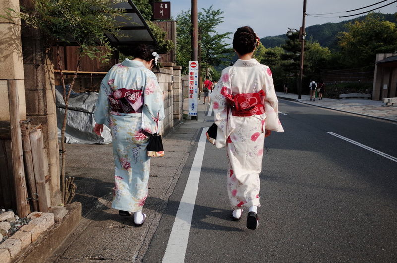 Rear view of geisha walking on road against cloudy sky