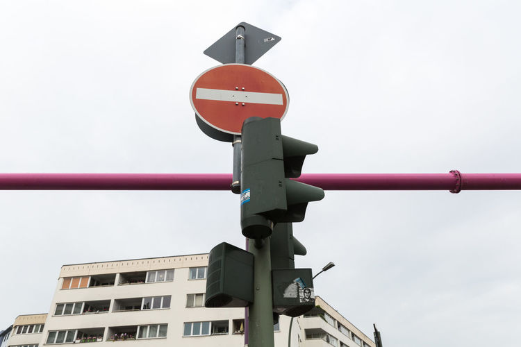 Low angle view of no entry sign board at road signal light against sky