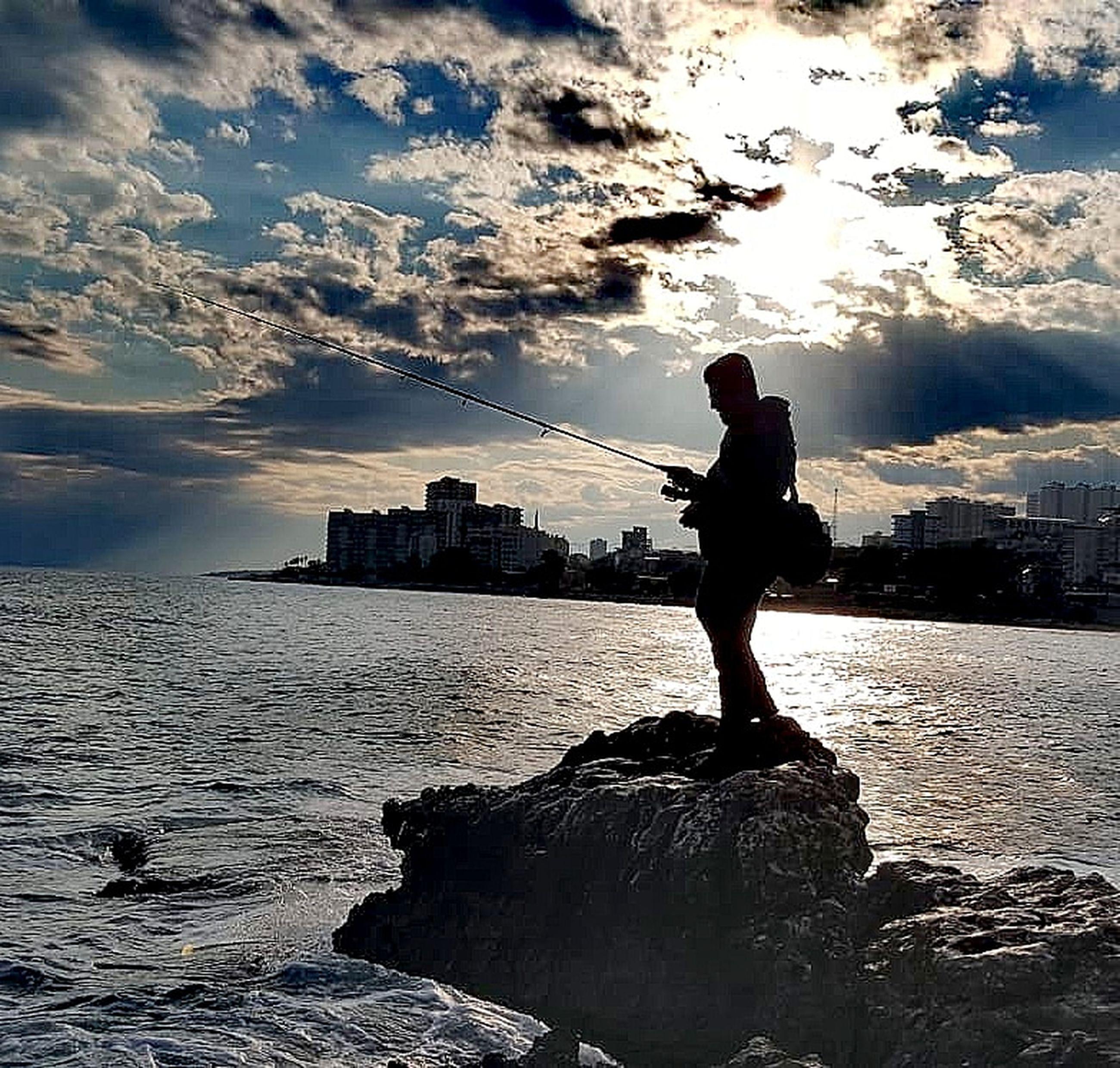 water, sky, one person, sea, standing, cloud - sky, built structure, architecture, real people, building exterior, rock, rock - object, nature, full length, lifestyles, solid, leisure activity, city, outdoors