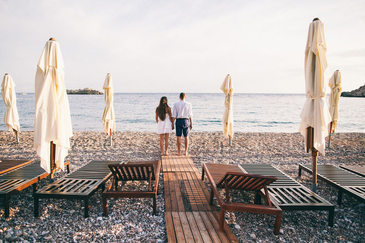 Rear View Of Couple Standing At Beach Against Clear Sky
