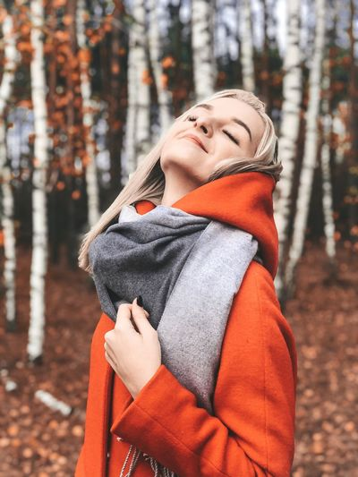 Midsection of woman standing by tree during winter