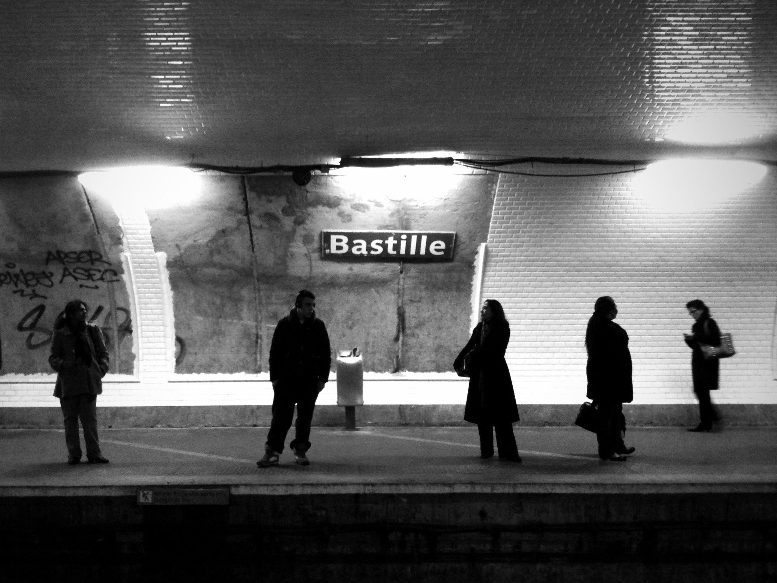 indoors, men, text, walking, person, lifestyles, western script, full length, railroad station, illuminated, subway station, built structure, architecture, subway, communication, large group of people, city life, railroad station platform, silhouette