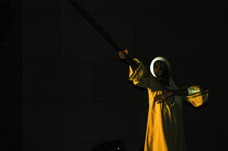 Low angle view of person holding umbrella at night