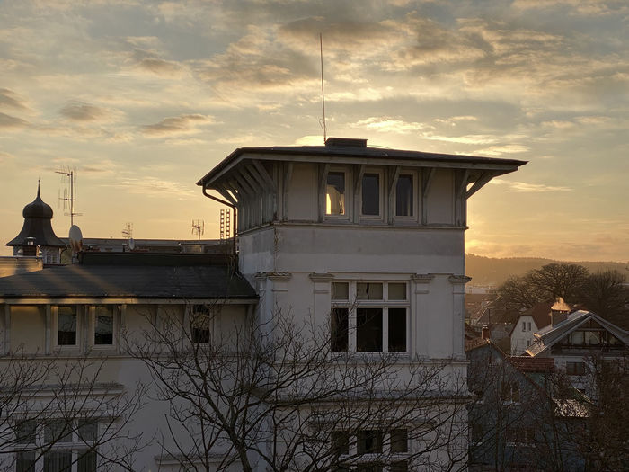 House by building against sky during sunset
