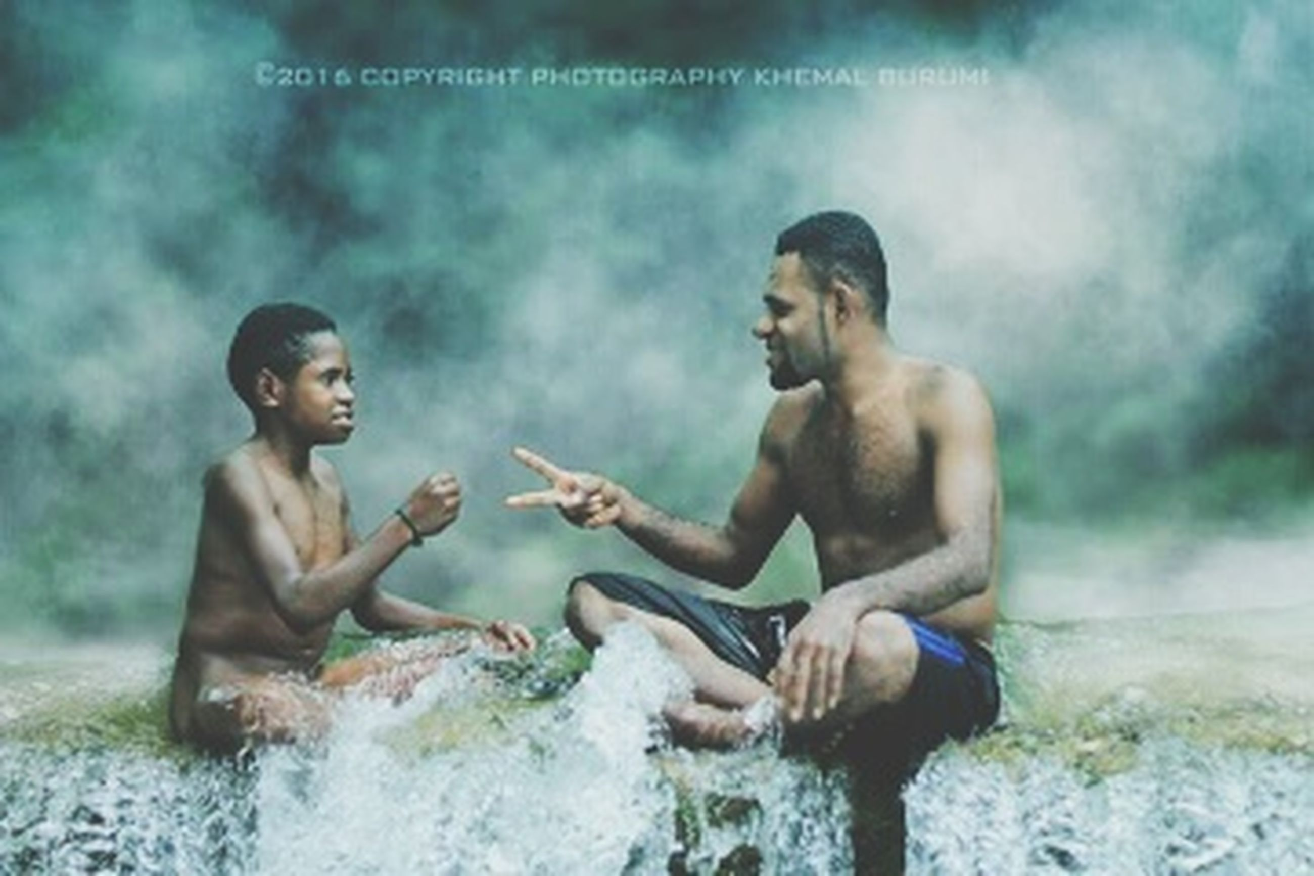 two people, men, shirtless, side view, water, males, smoke - physical structure, child, togetherness, people, childhood, nature, adult, offspring, young adult, sitting, emotion, family, semi-dress, son