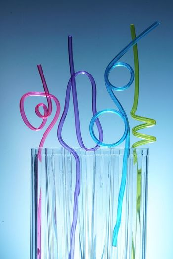 Close-up of colorful straws in glass against blue background