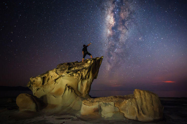 milky way galaxy. standing stone. starry night sky. Astronomy Beauty In Nature Galaxy Milky Way Nature Night One Person Scenics - Nature Science Sea Sky Space Standing Star Star - Space Star Field Tranquil Scene Tranquility Water